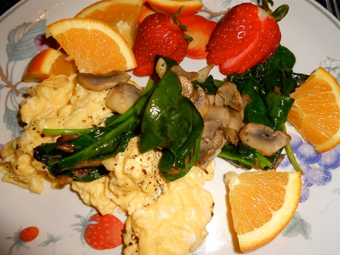Fresh fruits plus sautéed mushrooms and spinach over eggs""